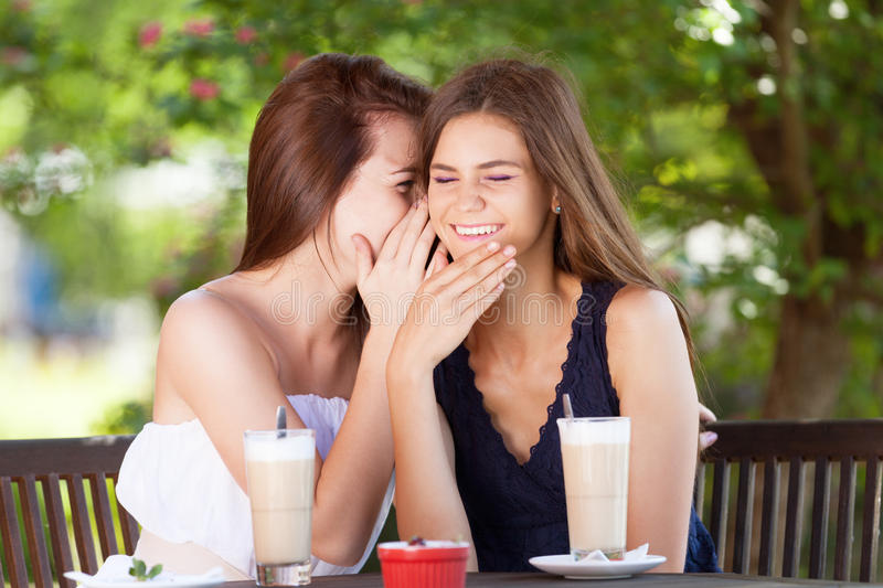 Gossips. Two girls gossiping in cafe royalty free stock photography