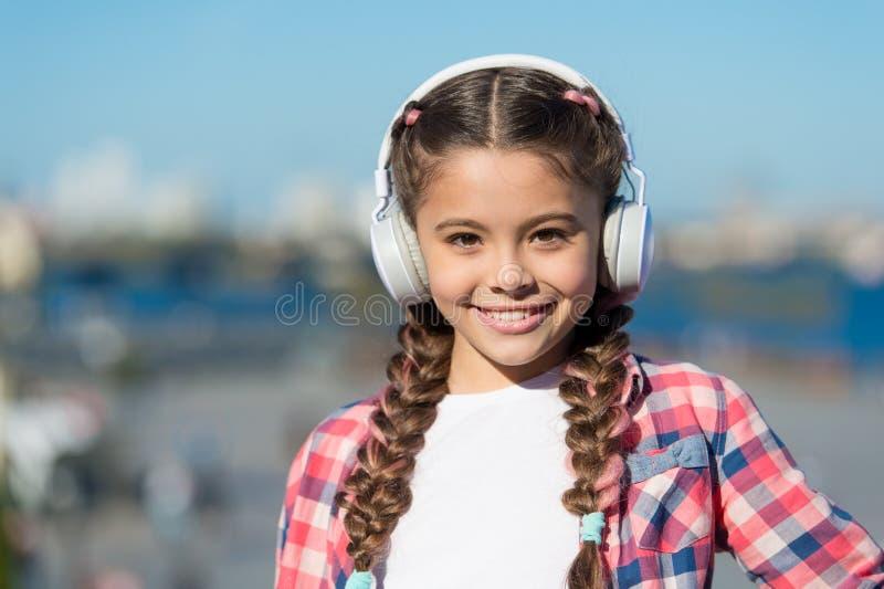 Gostar do que você faz é felicidade Fones de ouvido felizes do desgaste da criança Menina pequena feliz A menina pequena escuta a foto de stock