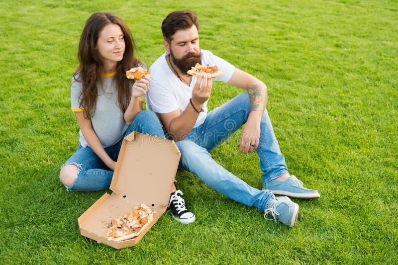 Gosto da satisfação piquenique do verão na grama verde Pares felizes que comem a pizza Alimento saud?vel Fast food Homem farpado fotos de stock royalty free