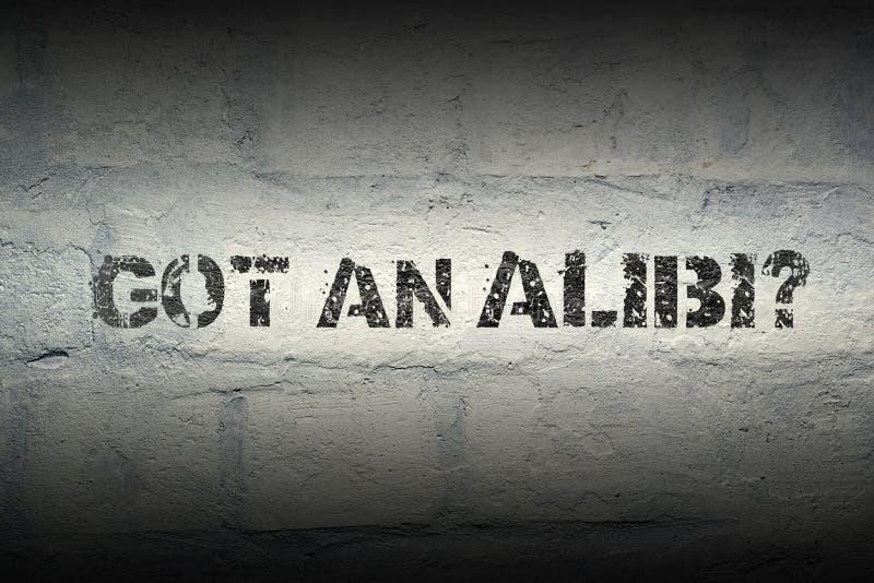 Got an alibi GR. Got an alibi stencil print on the grunge white brick wall stock images