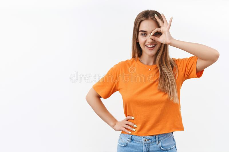 Got everything under control, no problem. Portrait of confident attractive girl assure all good, show okay sign over eye. And smiling broadly, hold hand on royalty free stock photos