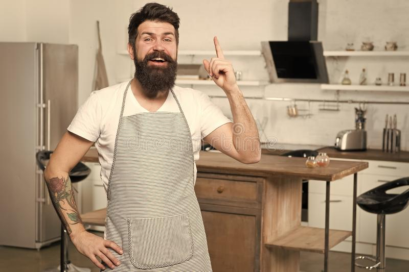 Got fresh idea about his recipe. Happy cook keeping finger raised in kitchen. Bearded chef following recipe to impress royalty free stock photo
