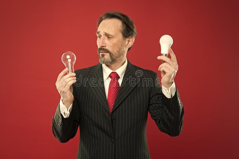 He got an idea. Power saving. confused male in business outfit. Electricity and energy. Man with beard search for. Inspiration. Businessman in suit hold light stock photo