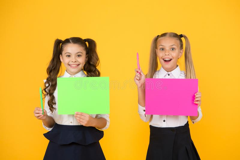 Got idea. Small cute kids smiling of genius idea. Happy girls holding paper sheets for writing idea on yellow background. Little children with empty paper for stock photography