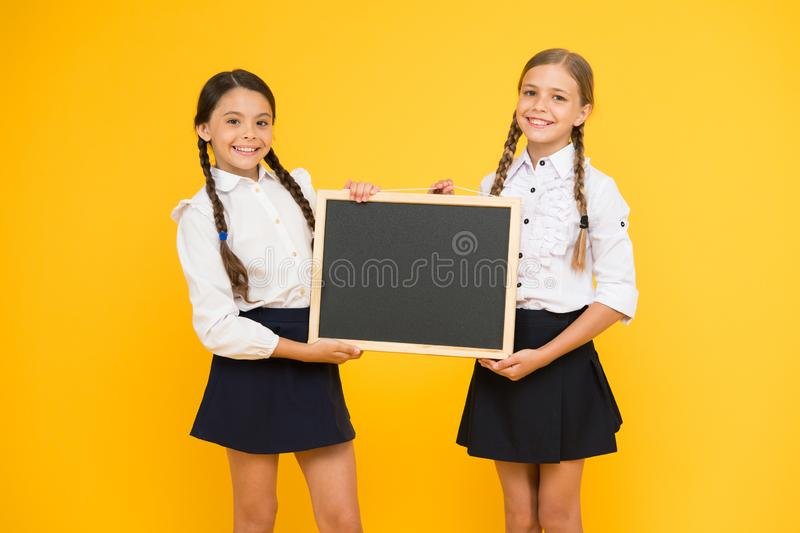 Got ready. Small pupils. Small girls holding blackboard on yellow background. Small schoolchildren with black-board for. Education. Small children preparing royalty free stock photography