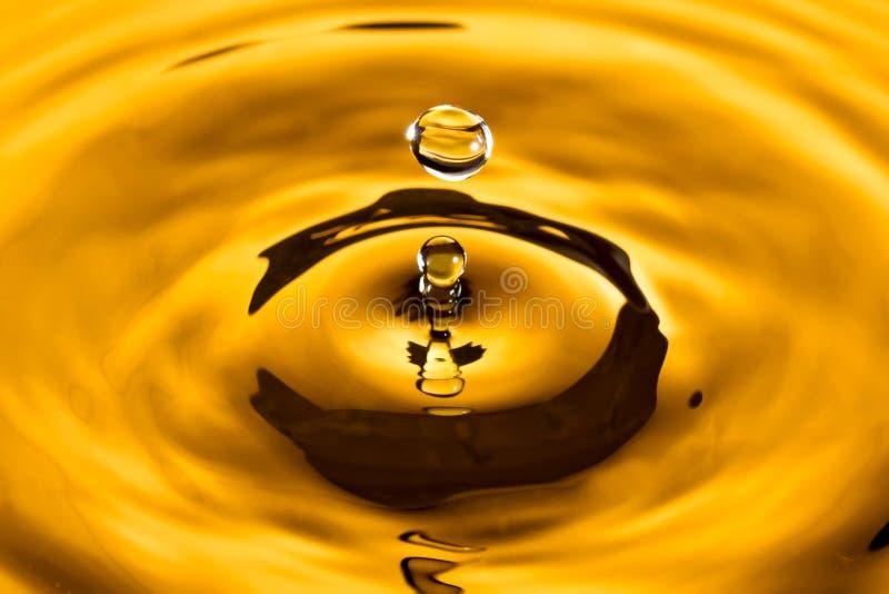 Gota amarela dourada da água fotografia de stock royalty free