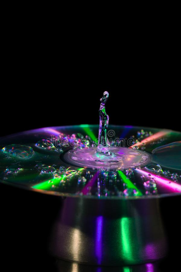 Gota da água em um CD com luzes coloridas imagens de stock