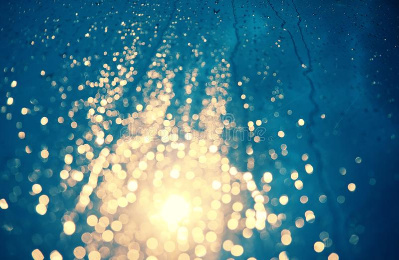 A gota da chuva na janela, sinal na noite faz o bokeh imagens de stock