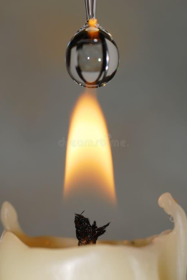 Gota de água que cai em uma flama de vela foto de stock