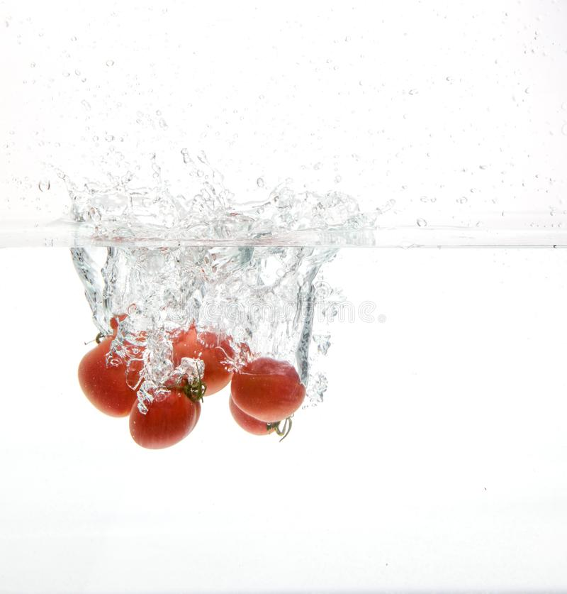 Gota de los tomates en agua fotografía de archivo libre de regalías