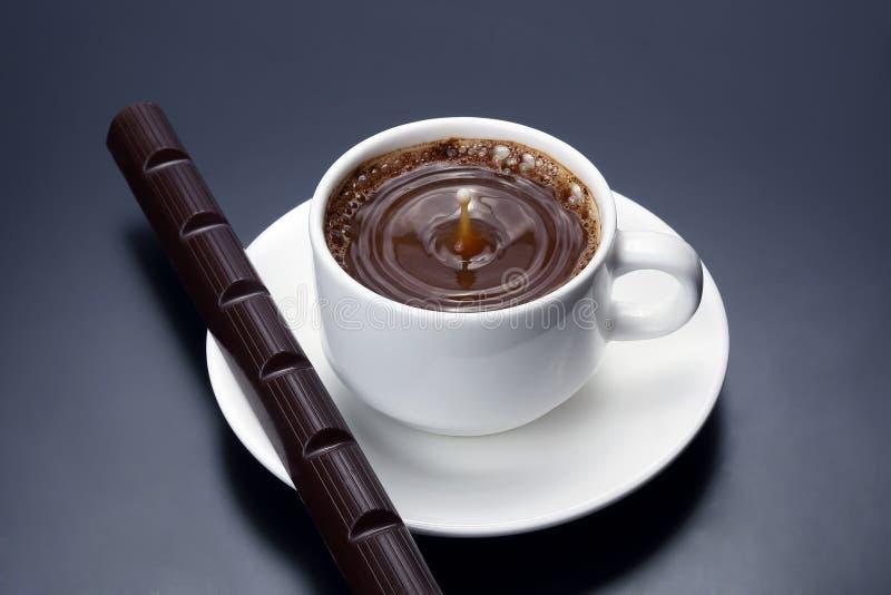Gota do leite que cai em um copo branco com café preto imagem de stock royalty free