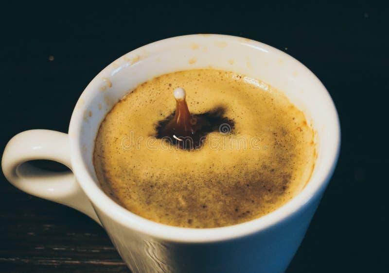 Gota do leite que cai em uma xícara de café fotos de stock royalty free