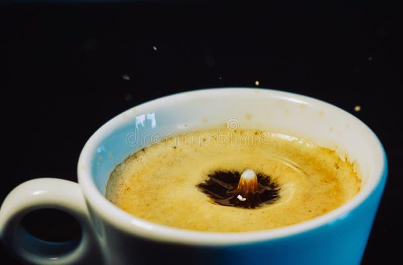 Gota do leite que cai em uma xícara de café imagens de stock royalty free