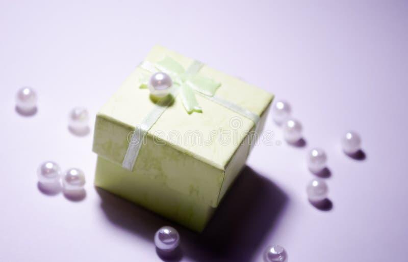 Gota en la caja Gota plástica Gotas del placer Granos blancos Gotas artificiales blancas de la perla Perlas de imitación Un montó foto de archivo libre de regalías