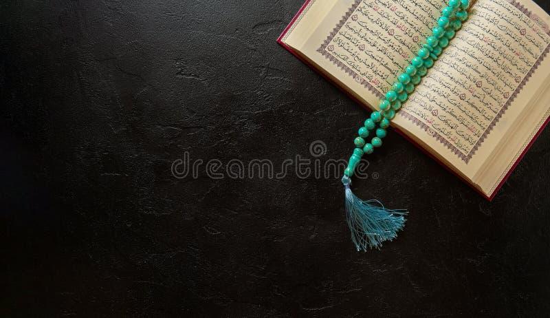 Gotas abiertas del Quran y del rosario en fondo negro de la textura de la piedra o de la pizarra Concepto islámico con el espacio foto de archivo libre de regalías