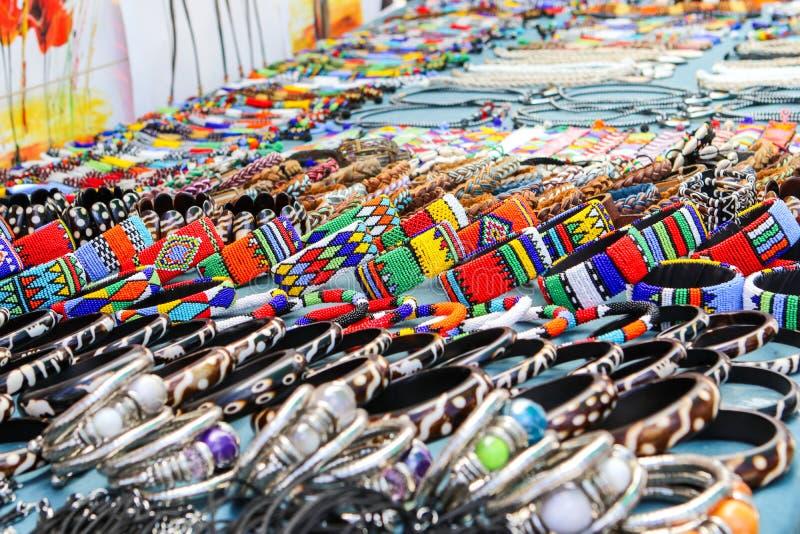 Gotas coloridas y pulseras, brazaletes y collares hechos a mano de cuero en el mercado local del arte en Suráfrica imagen de archivo