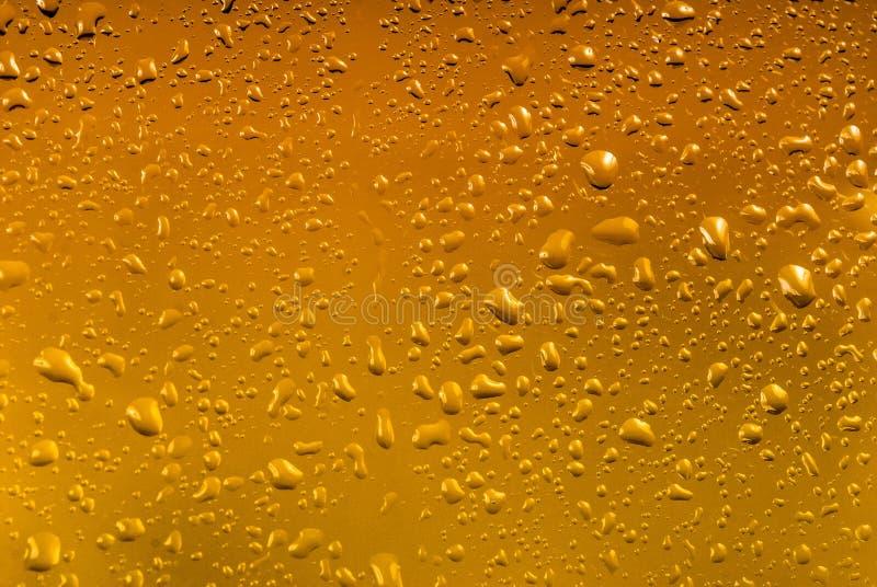 Gotas da água em um fundo amarelo da cor imagens de stock royalty free