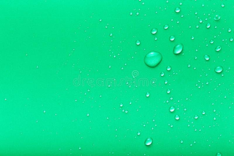 Gotas da água em um fundo da cor Verde toned foto de stock
