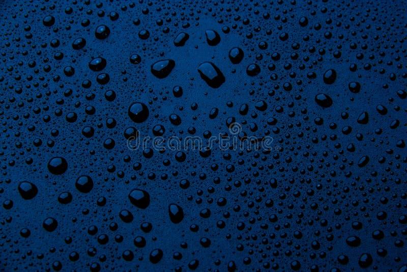 Gotas da água em um fundo da cor azul foto de stock royalty free