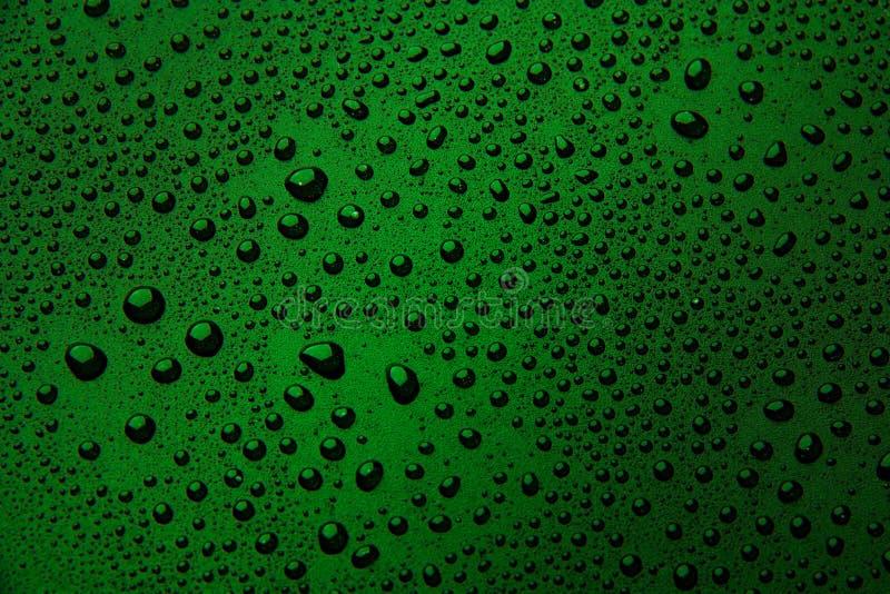 Gotas da água em um fundo da cor Verde fotografia de stock