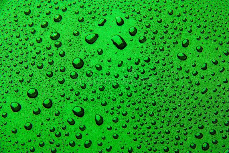 Gotas da água em um fundo da cor Verde foto de stock