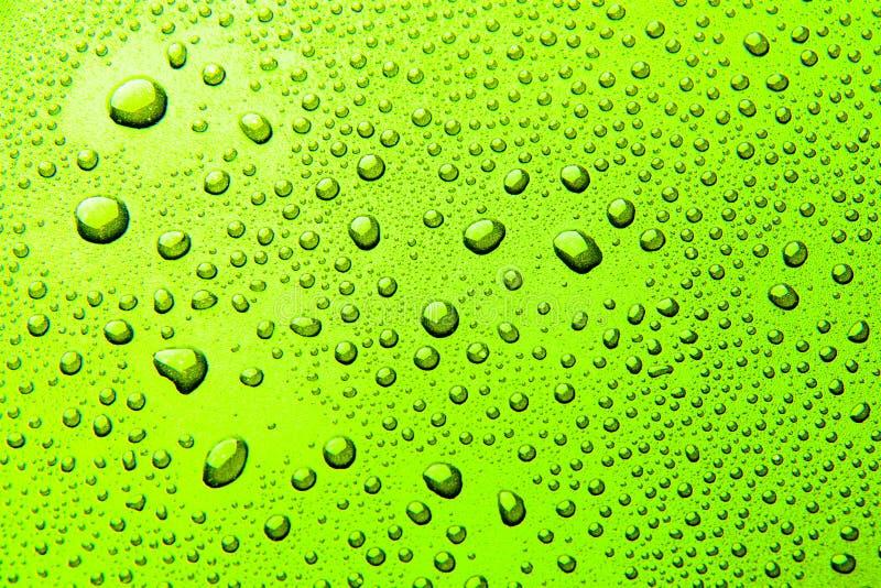 Gotas da água em um fundo da cor Verde imagens de stock