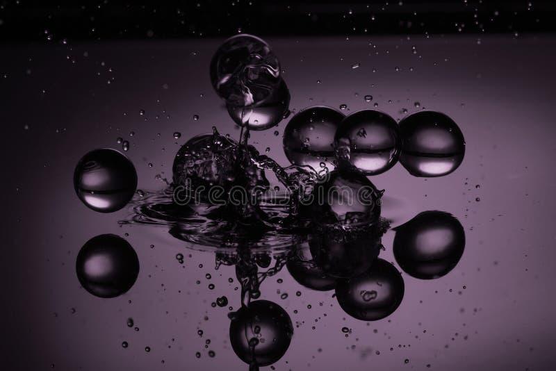 Gotas da água em um fundo roxo fotografia de stock