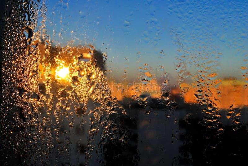 Gotas da água em um vidro de indicador após a chuva O céu com nuvens e sol no fundo imagens de stock