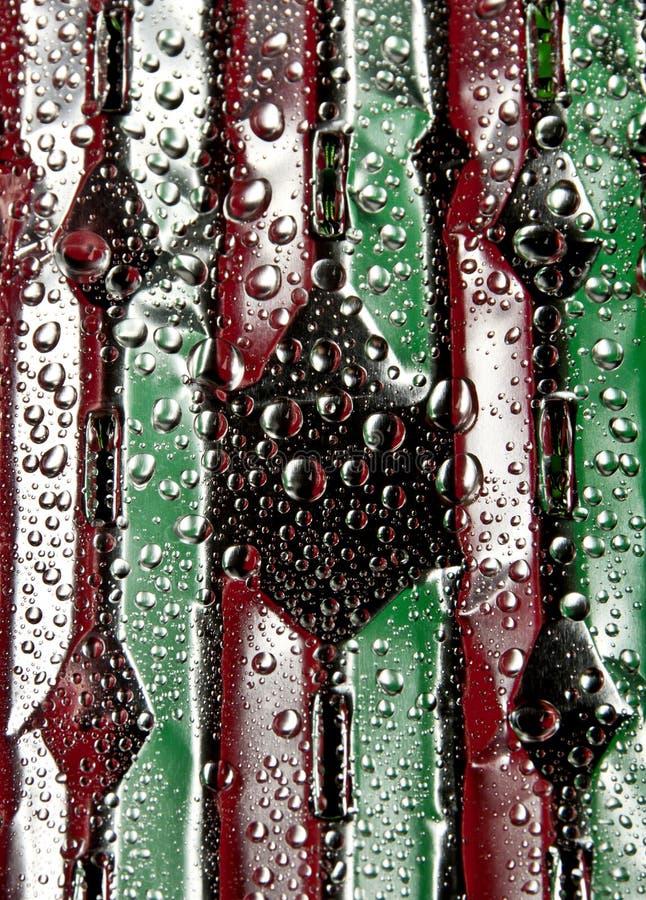 Gotas da água fresca em um verde e em um delicado vermelho bebida-como a superfície de alumínio imagens de stock