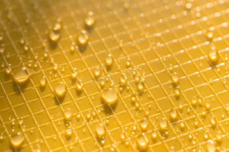 Gotas da água na textura plástica amarela do fundo fotos de stock