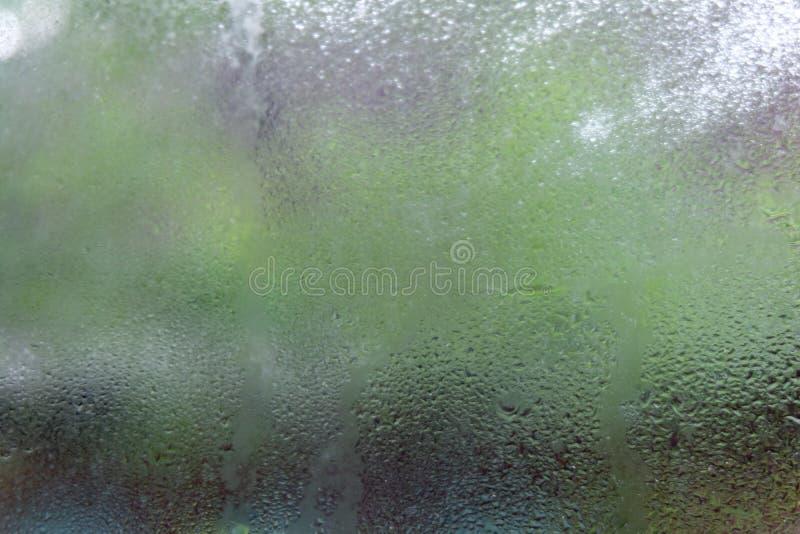 Gotas da água ou gota da chuva no vidro no borrado com fundos fotos de stock