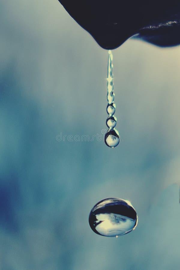 Gotas da água que fluem do telhado imagens de stock royalty free