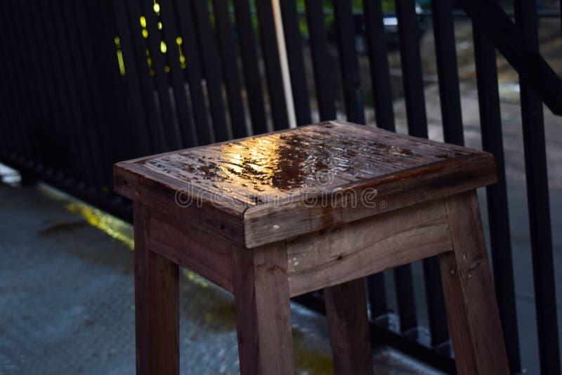 Gotas da chuva do close up com cadeira de madeira imagem de stock royalty free