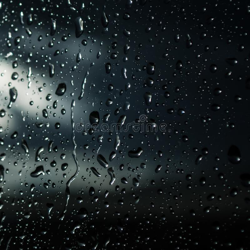 Gotas da chuva no fundo de vidro azul fotografia de stock