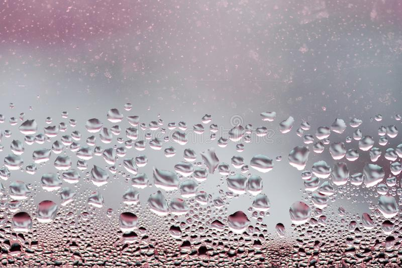 Gotas da chuva no fundo de vidro azul Luzes de Bokeh da rua fora de foco Contexto abstrato fotos de stock