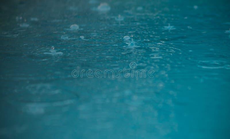 Gotas da chuva que caem dentro à água fotografia de stock royalty free