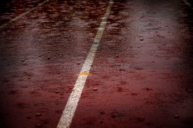 Gotas da chuva que caem na pista de atletismo da raça que atrasa competições imagem de stock