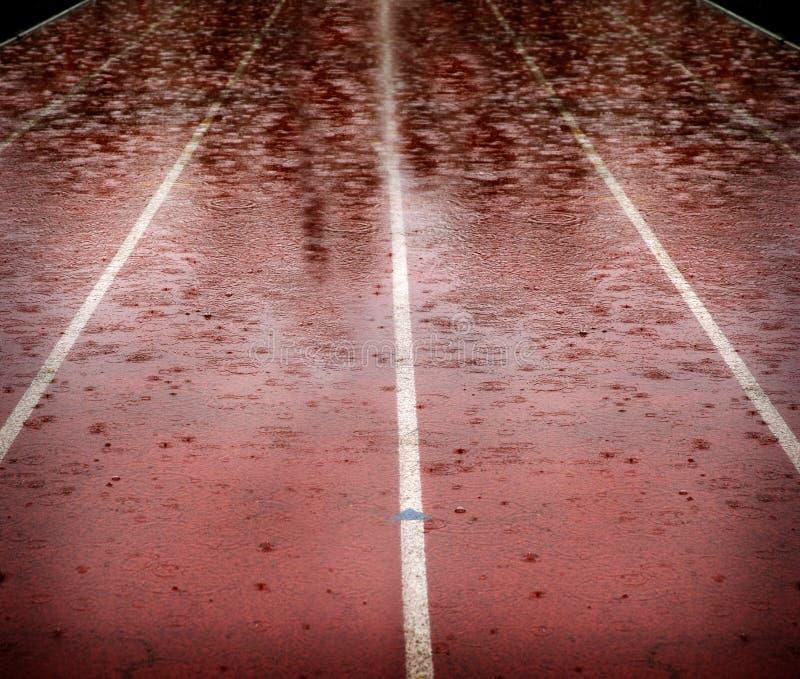 Gotas da chuva que caem na pista de atletismo da raça que atrasa competições fotos de stock