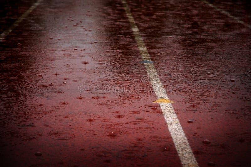 Gotas da chuva que caem na pista de atletismo da raça que atrasa competições foto de stock royalty free