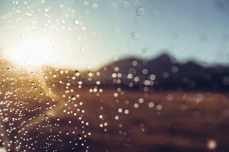 Gotas de agua en el escudo de viento del ` s del coche el las montañas y Sun, foco selectivo Concepto del viaje del viaje fotos de archivo libres de regalías