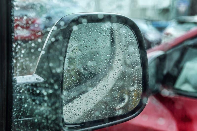 Gotas de agua en el espejo de la vista lateral del coche Primer foto de archivo