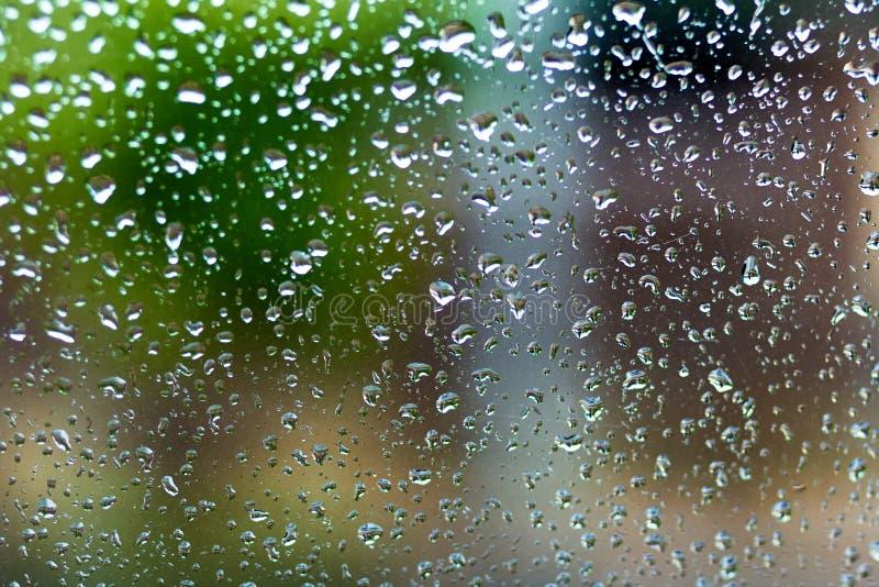 Gotas de agua en el vidrio de la ventana con el fondo de la falta de definición foto de archivo libre de regalías