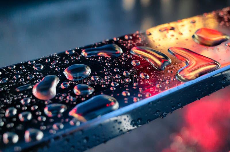 Gotas de agua en la superficie de la barandilla del metal o del acero inoxidable en las luces de color claro Fotografía del prime imágenes de archivo libres de regalías