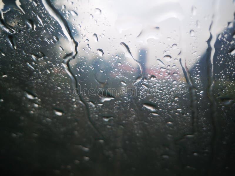 Gotas de agua en una ventana con la nube de la oscuridad fotografía de archivo