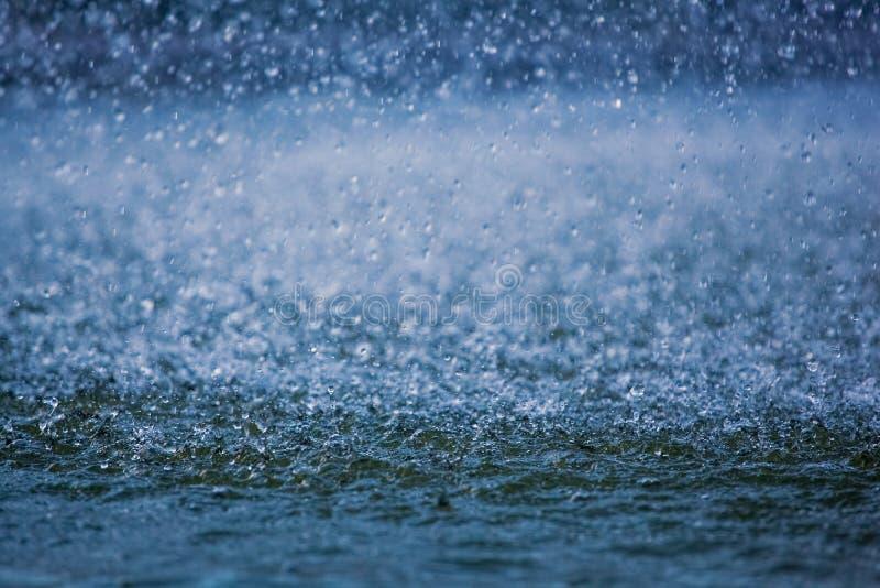 Gotas de agua que corren abajo en un charco, salpicando el agua visible fotos de archivo