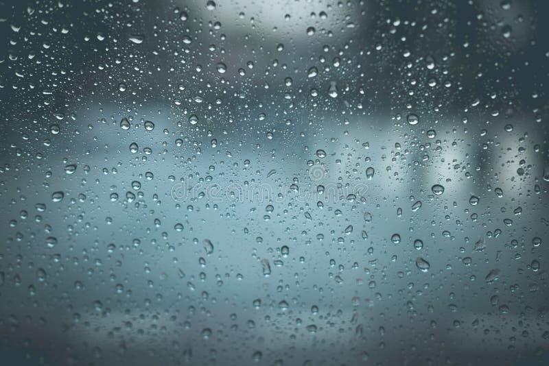 Gotas de la lluvia en fondo de cristal azul foto de archivo