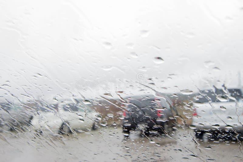 Gotas de la lluvia en la ventana del coche con la falta de definición del tráfico foto de archivo