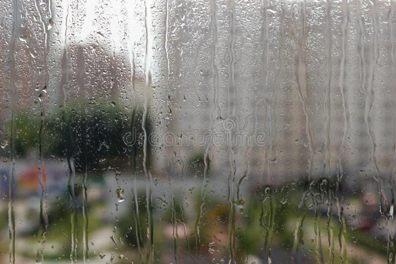 Gotas de la lluvia sobre el vidrio contra fondo de la ciudad foto de archivo
