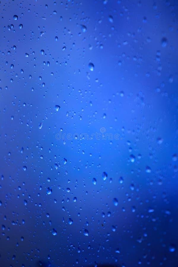 Gotas de la lluvia sobre un vidrio en un fondo azul imágenes de archivo libres de regalías