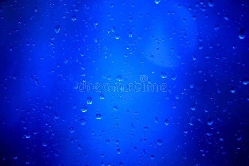 Gotas de la lluvia sobre un vidrio en un fondo azul imagen de archivo